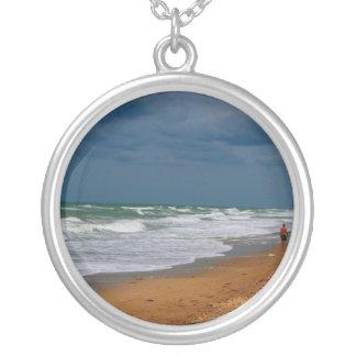 Hombre solitario que camina en la playa tempestuos joyeria