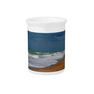 Hombre solitario que camina en la playa tempestuos jarra