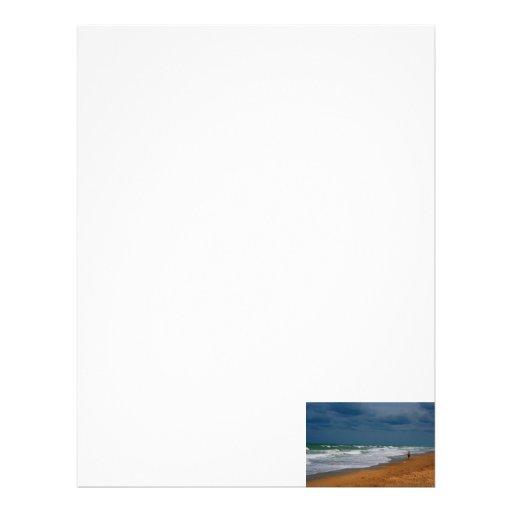 Hombre solitario que camina en la playa tempestuos membrete