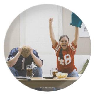 Hombre y mujer que se sientan en fútbol de plato