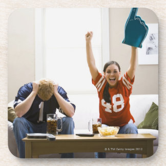Hombre y mujer que se sientan en fútbol de posavasos de bebida