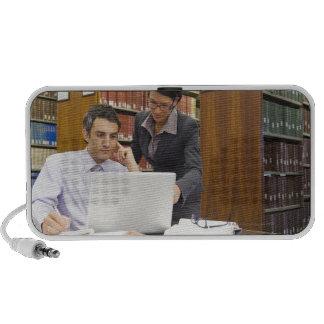 Hombres de negocios que hacen la investigación en  laptop altavoces