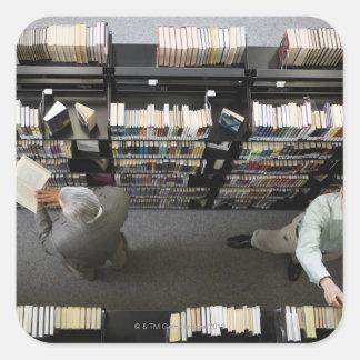 Hombres en la biblioteca que busca los libros pegatinas cuadradases
