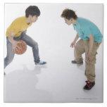 Hombres jovenes que juegan a baloncesto azulejo
