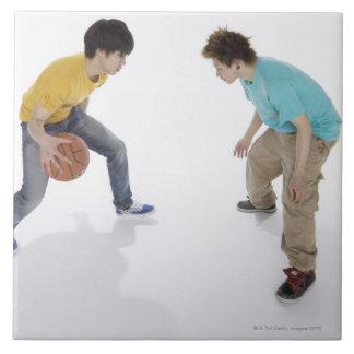 Hombres jovenes que juegan a baloncesto azulejo cuadrado grande