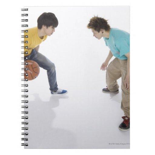 Hombres jovenes que juegan a baloncesto libros de apuntes con espiral