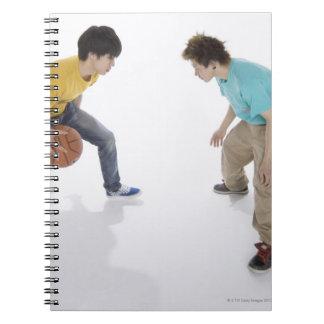 Hombres jovenes que juegan a baloncesto spiral notebooks