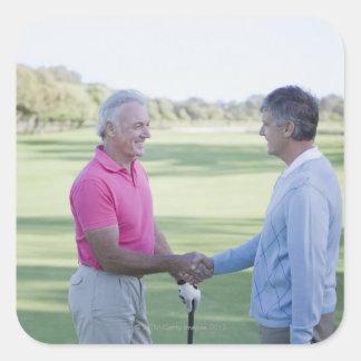 Hombres que sacuden las manos en campo de golf pegatina cuadrada