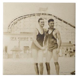 Hombres que se colocan en la playa azulejo cuadrado grande