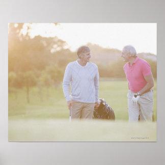 Hombres que tiran de los carros de golf póster