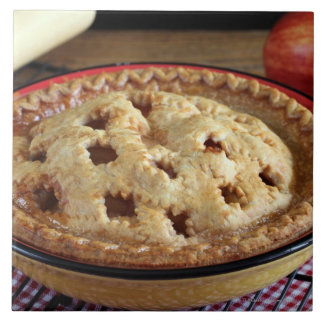 Home baked apple pie on cooling rack with apple ceramic tile