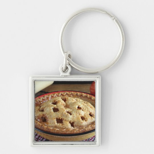 Home baked apple pie on cooling rack with apple keychain