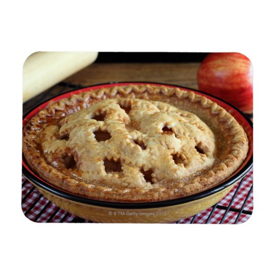 Home baked apple pie on cooling rack with apple magnet