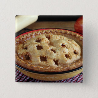 Home baked apple pie on cooling rack with apple pinback button