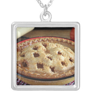 Home baked apple pie on cooling rack with apple square pendant necklace