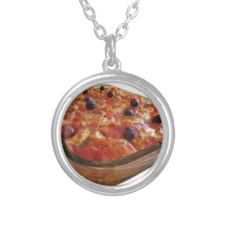 Home made baked pasta on white background silver plated necklace