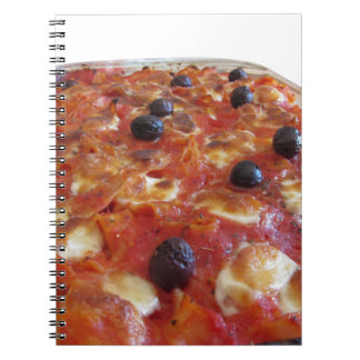 Home made baked pasta on white background spiral notebook