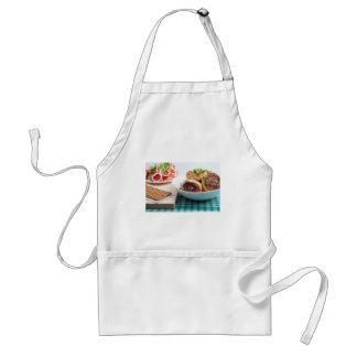 Homemade fried meatballs in a white bowl closeup adult apron