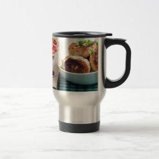 Homemade fried meatballs in a white bowl closeup travel mug