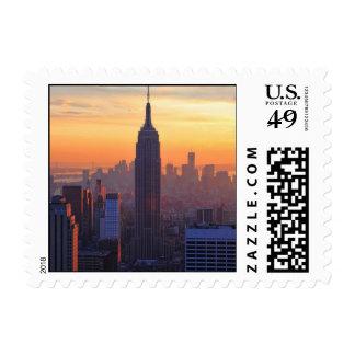 Horizonte de NYC: Puesta del sol anaranjada del Estampillas