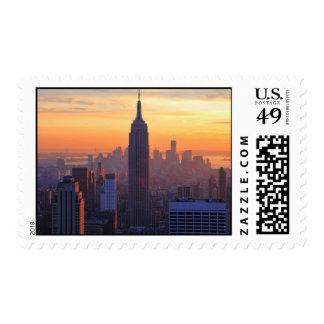 Horizonte de NYC: Puesta del sol del naranja del Sellos