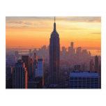 Horizonte de NYC: Puesta del sol del naranja del Postal