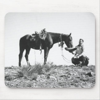 Horse eating from a cowboy's hat. mouse pad