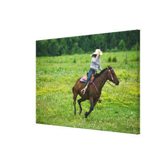Horseback rider galloping in rural pasture gallery wrap canvas