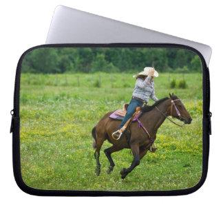 Horseback rider galloping in rural pasture laptop sleeve