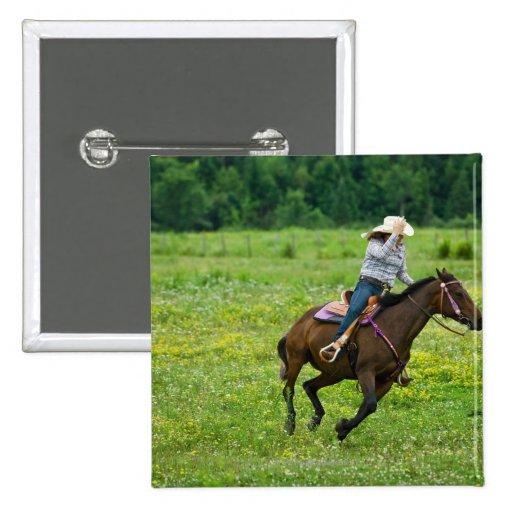 Horseback rider galloping in rural pasture pins