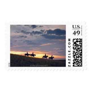 Horseback riders at sunset 2 postage stamp