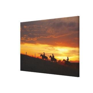 Horseback riders at sunset canvas print