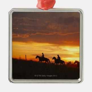Horseback riders at sunset metal ornament