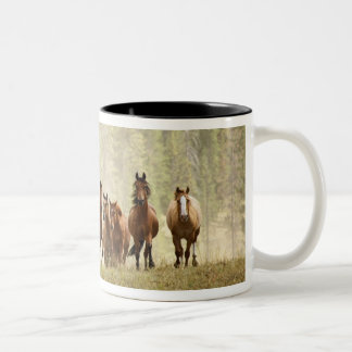 Horses cresting small hill during roundup, Two-Tone coffee mug