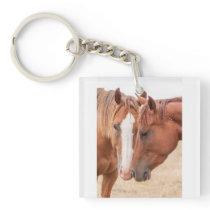 Horses nuzzling in a pasture keychain