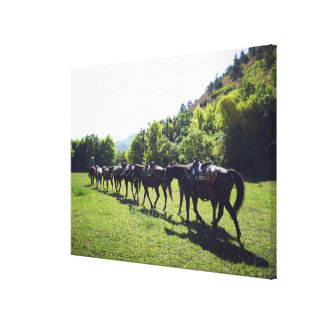 Horses walking in a line canvas print
