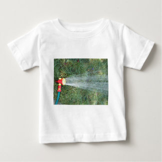 Hose with a spray watering the lawn closeup infant t-shirt