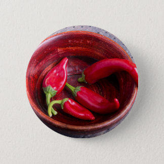 Hot red chili peppers on a fabric background button