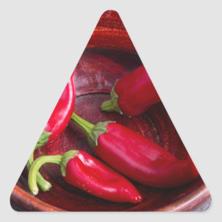 Hot red chili peppers on a fabric background triangle sticker