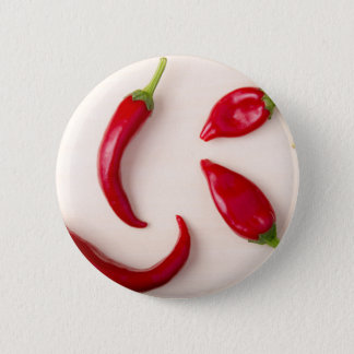 Hot red chili peppers on a light wooden board button