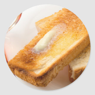 Hot toast with butter on a white plate close-up classic round sticker