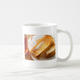 Hot toast with butter on a white plate close-up coffee mug