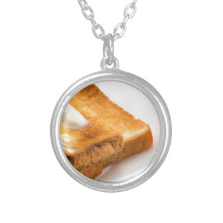 Hot toast with butter on a white plate silver plated necklace