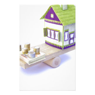 House in balance with pile of euro coins and notes stationery