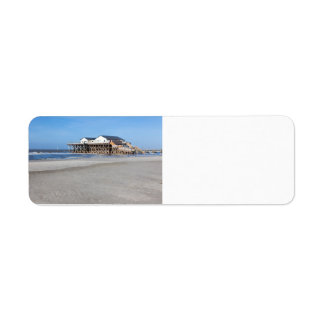 House on stilts at the beach of St. Peter Ording Label