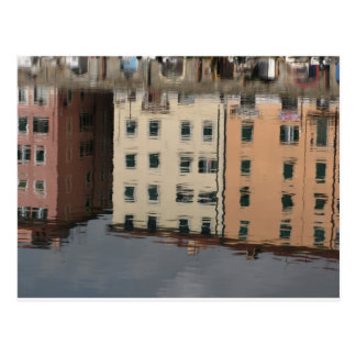 Houses are reflected in the tranquil water postcard