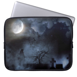 Howling wolf in a moonlit cemetery laptop sleeve