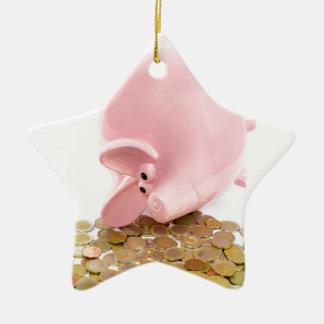Hucha rosada que está situada con la pila de adorno navideño de cerámica en forma de estrella