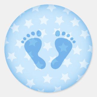 Huellas del bebé azul en un fondo estrellado etiqueta redonda
