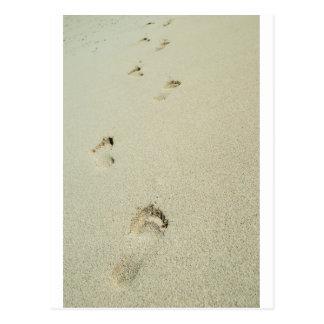 Huellas descalzas en la arena postal